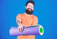 Yoga class concept. Yoga as hobby and sport. Practicing yoga every day. Man bearded athlete hold fitness mat. Fitness. And stretching. Having good stretch royalty free stock image