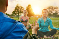 Yoga class of diverse millennials on the grass at sunset in nature park. Yoga fitness coach leading a group into a relaxing meditation with the sunlight behind Royalty Free Stock Photo
