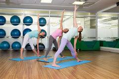 Yoga class in extended traingle position in fitness studio Stock Photos