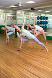 Yoga class in extended triangle pose in fitness studio Royalty Free Stock Images