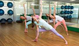 Yoga class in extended triangle pose in fitness studio Stock Photos