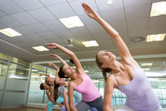 Yoga class in extended triangle pose in fitness studio Stock Photo