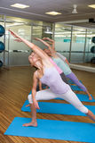 Yoga class in extended triangle pose in fitness studio. At the leisure center Stock Photography