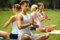 Yoga Class. Group of People Meditating At Summer Park Stock Photos
