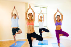 Yoga Class. Group of Young People Relaxing Practicing Yoga, Healthy Lifestyle Stock Images