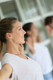 Yoga class guided by a woman. Attractive blond women attending yoga course with group Stock Image