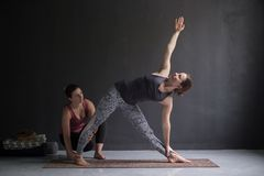 Yoga class instructor and beginner making asana exercises. Teacher assists to make triangle pose, trikonasana. Healthy stretching with coach stock images