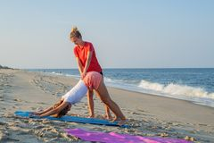 Yoga class instructor helps beginner to make asana exercises. Woman doing downward facing dog exercise with trainer on the beach stock image
