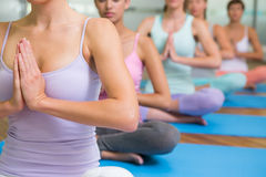 Yoga class in lotus pose in fitness studio Stock Photos