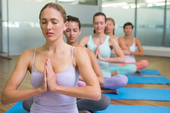 Yoga class in lotus pose in fitness studio Stock Image