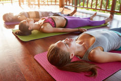 Yoga class lying in the Corpse pose, Savasana Stock Photos