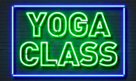 Yoga class neon sign on brick wall background. stock photos