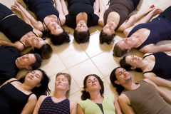 Yoga class relaxing. In the 'Corpse pose - savasana'. The group is lying in a circle with heads to the inside stock photos