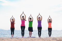 Yoga class at sea beach in evening ,Group of people doing namast Royalty Free Stock Image