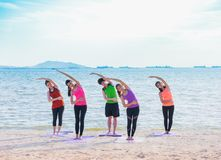Yoga class at sea beach in evening ,Group of people doing Standi Stock Photos