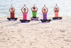 Yoga class at sea beach in evening ,Group of people doing tree poses with relax emotion at beach,Meditation pose,Wellness and royalty free stock image