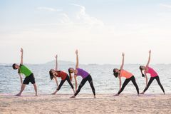 Yoga class at sea beach in evening ,Group of people doing Triang Stock Photography
