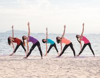 Yoga class at sea beach in evening ,Group of people doing Triang Royalty Free Stock Photography