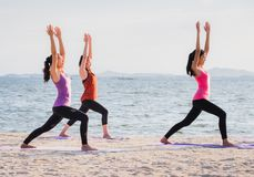 Yoga class at sea beach in evening ,Group of people doing Warrio Royalty Free Stock Photos