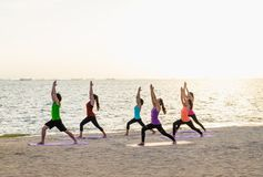 Yoga class at sea beach in sunset time ,Group of people doing Wa Stock Images