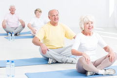 Yoga class for seniors. Group of seniors attending yoga class and sitting at exercising mats Stock Images