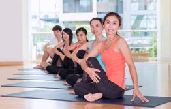 Yoga class in studio room,Group of people doing seated Half Lord Stock Image