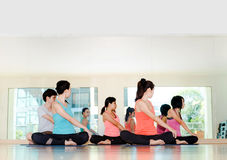 Yoga class in studio room,Group of people doing seated twist pos. E with clam relax emotion,Meditation pose,Wellness and Healthy Lifestyle Stock Photos