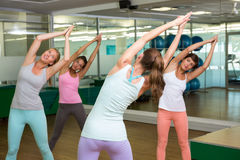 Yoga class in tree pose in fitness studio Stock Images