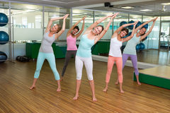 Yoga class in tree pose in fitness studio Stock Photography