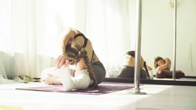Two women doing yoga asanas in studio. Yoga class. Two women doing yoga asanas in bright studio. Reflection in the mirror stock video footage