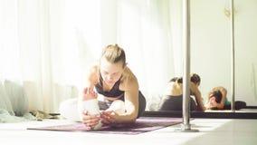 Two women doing yoga asanas in studio. Yoga class. Two women doing yoga asanas in bright studio. Reflection in the mirror stock footage