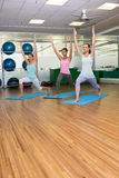 Yoga class in warrior pose in fitness studio Royalty Free Stock Photo