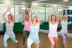 Yoga class in warrior pose in fitness studio Stock Photo