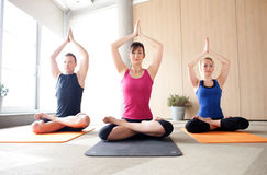 Yoga class. Young people meditating in a yoga class