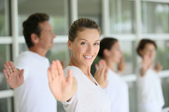 Yoga classes guided by a woman teacher. Attractive blond women attending yoga course with group Royalty Free Stock Image