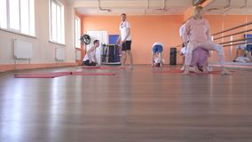 Yoga classes with an individual instructor with a beautiful caucasian girl in a modern fitness center, male friends. Doing yoga to reduce excess weight and stock video