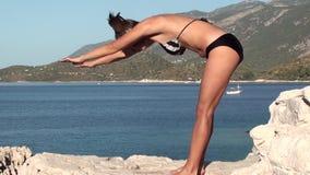 Yoga on cliffs Forward bent asana stock video footage