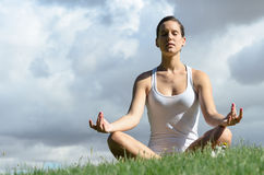 Yoga and Clouds. Young woman in white, relaxing and meditating on cloudy background Royalty Free Stock Photography