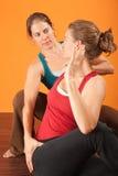 Yoga Coach. Yogasana coach with student stretching over orange background Stock Photo