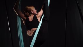 Yoga coach makes a vertical twine standing in a hammock. For air yoga, side view stock video footage