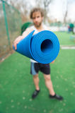 Yoga, colore blu della stuoia di forma fisica in mani dell'uomo muscolare Immagini Stock