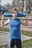 Yoga, colore blu della stuoia di forma fisica in mani dell'uomo muscolare Fotografie Stock