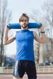Yoga, colore blu della stuoia di forma fisica in mani dell'uomo muscolare Immagine Stock Libera da Diritti