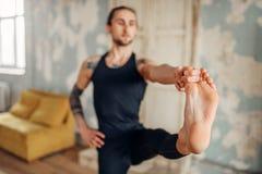 Yoga con il tatuaggio che fa allungando esercizio in palestra Immagini Stock