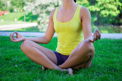 Yoga concept - close up of woman sitting in lotus pose in park Stock Images