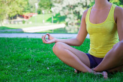 Yoga concept - close up of young woman sitting in lotus pose in Stock Photo