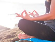 Yoga concept. Closeup woman hand practicing lotus pose on the beach at sunset Stock Photography