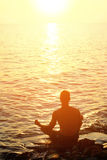 Yoga concept, silhouette of man meditating in lotus pose on the beach near the sea, ocean, during sunset Stock Images