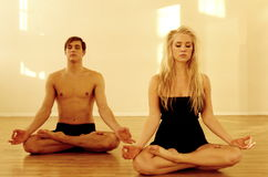 Yoga couple. Attractive couple meditating in yoga lotus pose Royalty Free Stock Photo