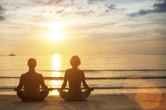 Yoga couple meditating on the coast during the amazing sunset. Young yoga couple meditating on the coast during the amazing sunset Royalty Free Stock Photo